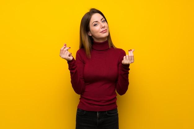 Vrouw met coltrui over gele muur die geldgebaar maken