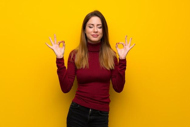 Vrouw met coltrui over gele muur in zen pose