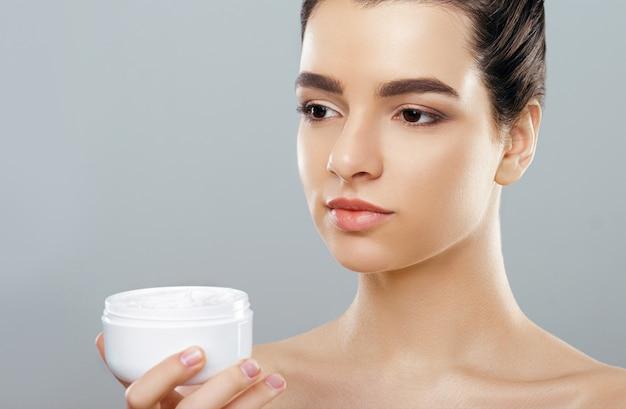 Vrouw met cosmetische crème. mooi gezicht. meisje met schone frisse huid. detailopname.