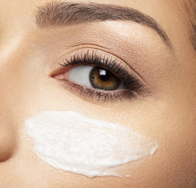 Vrouw met cosmetische crème-uitstrijkje op gezicht in de buurt van oog. huid zorg concept. schoonheidsbehandeling concept.