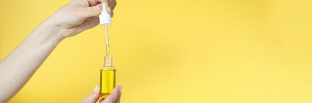Vrouw met cosmetische olie in haar handen op gele achtergrond close-up