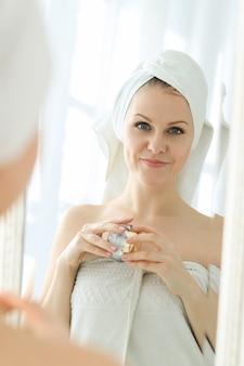 Vrouw met cosmetische producten en handdoek op haar hoofd na het douchen