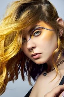 Vrouw met creatieve gele kleur haar en make-up met strass
