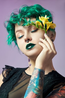 Vrouw met creatieve groene kleuren haar en make-up, giftige haren.
