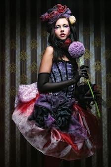 Vrouw met creatieve make-up in poppenstijl met bloem
