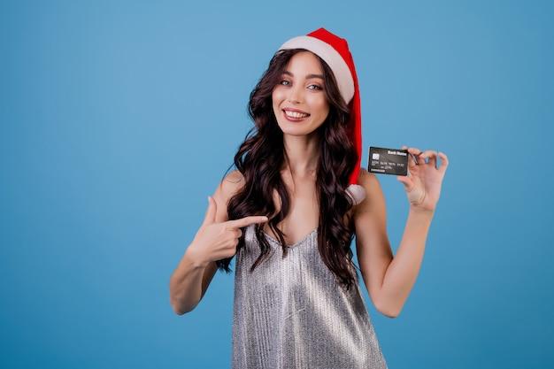 Vrouw met creditcard die geïsoleerde kerstmishoed draagt