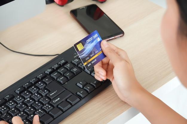 Vrouw met creditcard en computer die rekeningen online thuis betalen