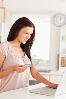 Vrouw met creditcard en kijken naar laptop