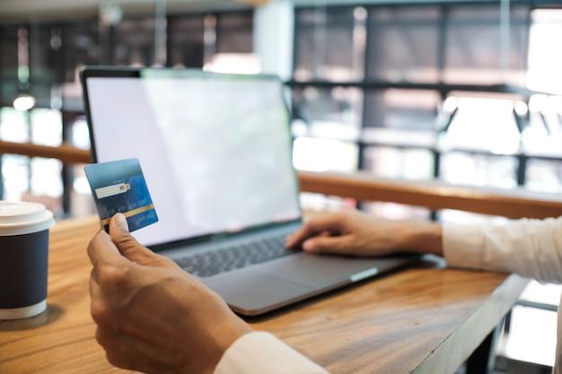 Vrouw met creditcard en met behulp van laptopcomputer