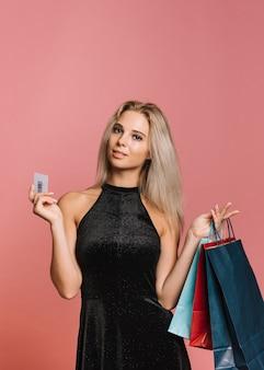 Vrouw met creditcard en papieren zakken