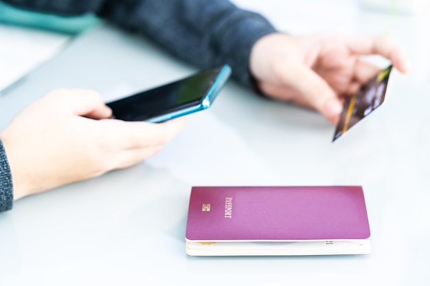 Vrouw met creditcard en paspoort met behulp van smartphone voor online winkelen op dek i