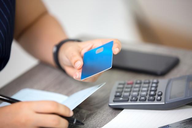 Vrouw met creditcard en rekenmachine rekeningen online betalen aan tafel