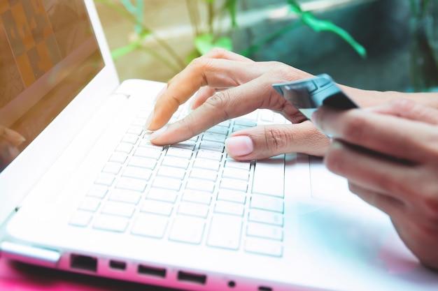 Vrouw met creditcard op laptop. online winkelen, online bankieren concept