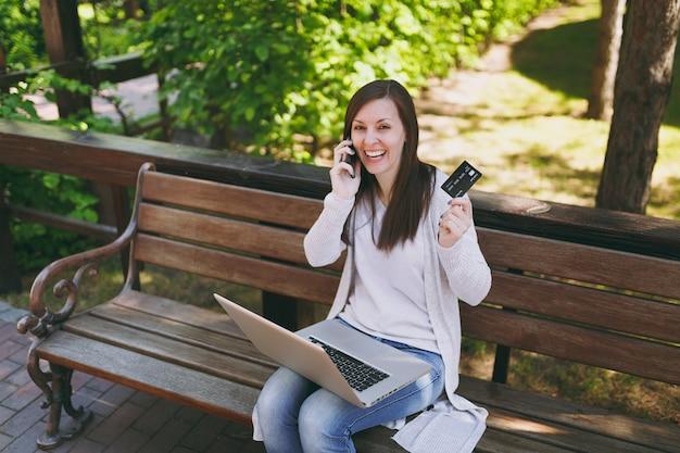 Vrouw met creditcard, praten op mobiele telefoon, met plezier een gesprek. vrouw zittend op een bankje bezig met moderne laptop in straat buiten. mobiel kantoor. freelance bedrijfsconcept.