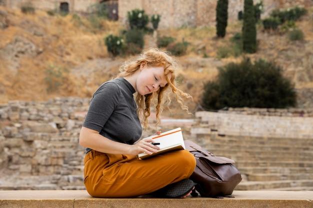 Vrouw met dagboek in de buurt van rugzak