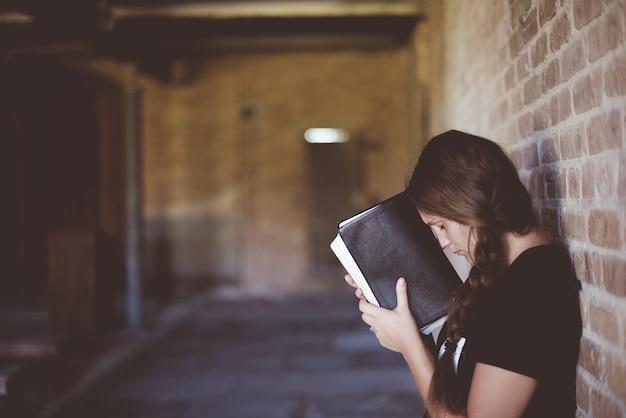 Vrouw met de bijbel tegen haar hoofd tijdens het bidden