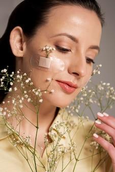 Vrouw met de bloem van de bandhulp op gezicht