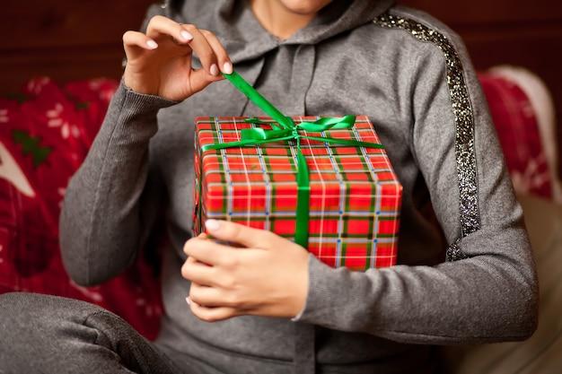 Vrouw met de doos van de kerstmisgift in handen.