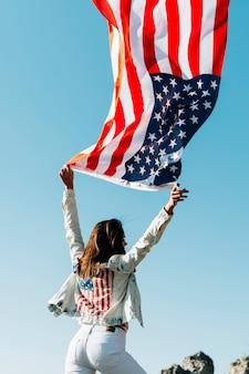 Vrouw met de golvende vlag van de vs op blauwe hemel