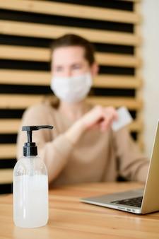 Vrouw met de holdingscreditcard van het gezichtsmasker
