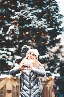 Vrouw met de kerstboom toont het hart