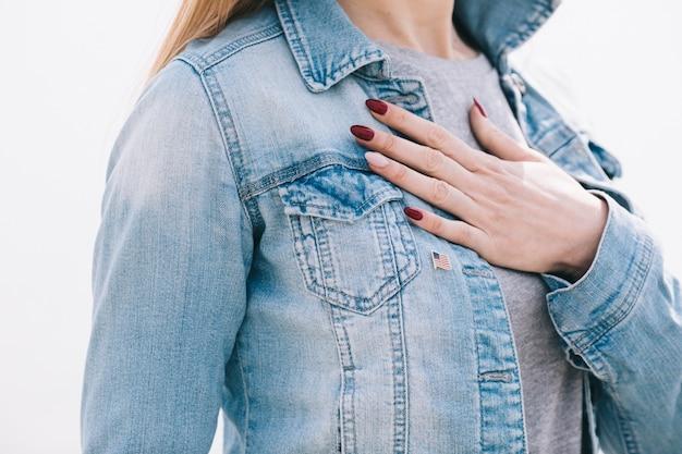 Vrouw met de linkerhand op de borst