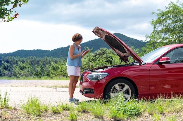 Vrouw met de motorkap van haar auto omhoog kijkend naar de motor
