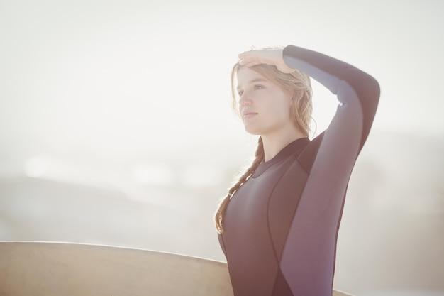 Vrouw met de ogen van de surfplankbescherming bij strand