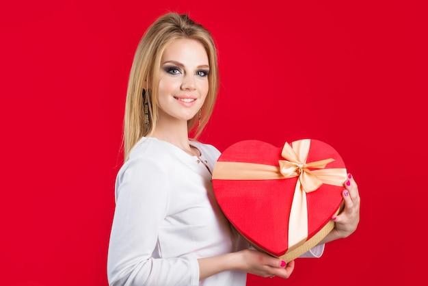 Vrouw met de rode gift van het valentijnskaartenhart. presenteer met liefde.
