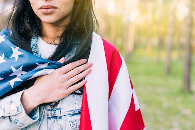 Vrouw met de vlag van de vs op de schouders