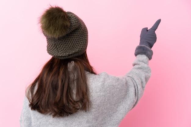 Vrouw met de winterhoed over geïsoleerde roze muur