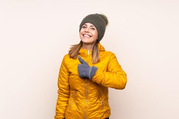 Vrouw met de winterhoed over muur geven duimen op gebaar