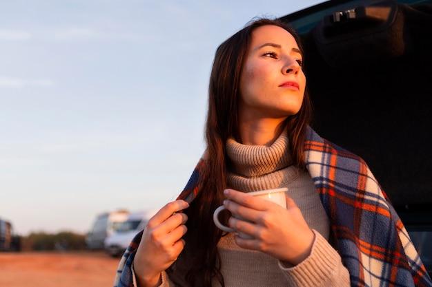 Vrouw met deken op buitenshuis genieten van kopje koffie