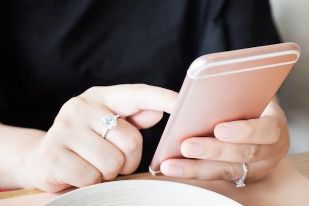 Vrouw met diamanten ring bij de hand met behulp van smartphone