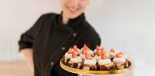 Vrouw met dienblad met dessert close-up