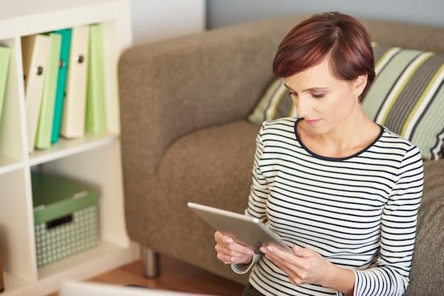 Vrouw met digitale tablet naast de bank