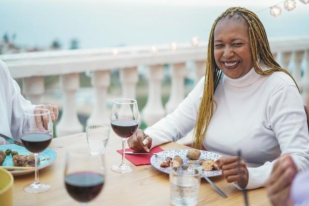 Vrouw met diner en wijn drinken met vrienden bij barbecue in restaurant