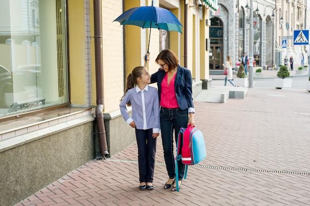 Vrouw met dochter die samen naar school onder een paraplu loopt.