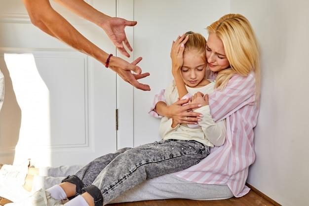 Vrouw met dochter zit die lijdt aan wreedheid van vader, concept van misbruikrelaties, man schreeuwt en straft familieleden