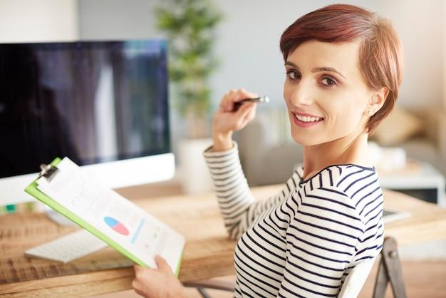 Vrouw met documenten die naar de camera kijken