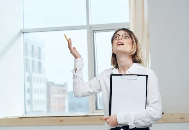 Vrouw met documenten in handen dichtbij het venster binnen bedrijfsfinanciën