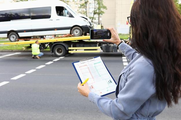 Vrouw met documenten in handen fotograferen van vernielde auto op telefoon