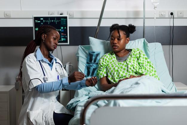 Vrouw met doktersberoep die röntgenresultaten vasthoudt met patiënt in ziekenhuisafdeling. afro-amerikaanse dokter, chirurg die radiografie toont aan jonge persoon die in bed ligt. specialist genezende ziekte