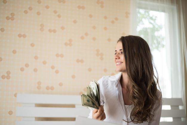 Vrouw met dollarbankbiljet op het bed