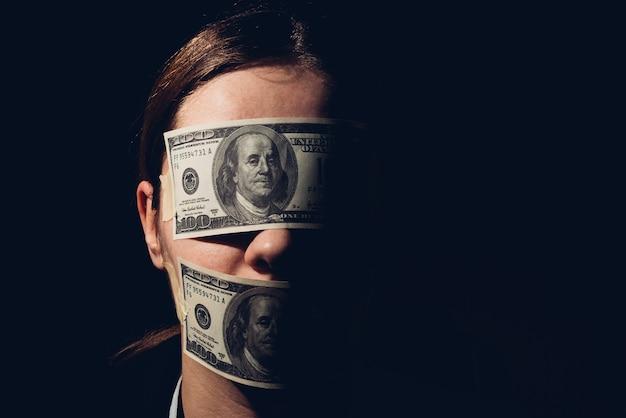 Vrouw met dollarbiljetten die haar ogen bedekken