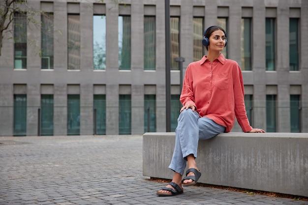 Vrouw met donker haar draagt comfortabele casual kleding kijkt weg luistert muziek in koptelefoon poses op stenen plaat in de buurt van modern gebouw. mensen levensstijl en hobby concept