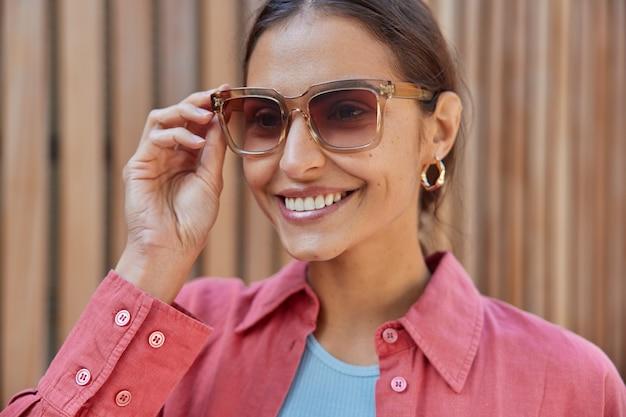 Vrouw met donker haar houdt hand op zonnebril gekleed in roze shirt geconcentreerd in afstand voelt zich gelukkig geniet van zonnige dag en recreatietijd. vrouwen en stijl