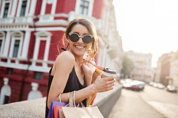 Vrouw met donker haar in bruine bril en zwarte jurk wandelen in de stad