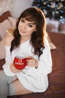 Vrouw met donker haar, lichte make-up in een modieuze gezellige trui en kousen met kopje koffie ingericht voor kerstkamer