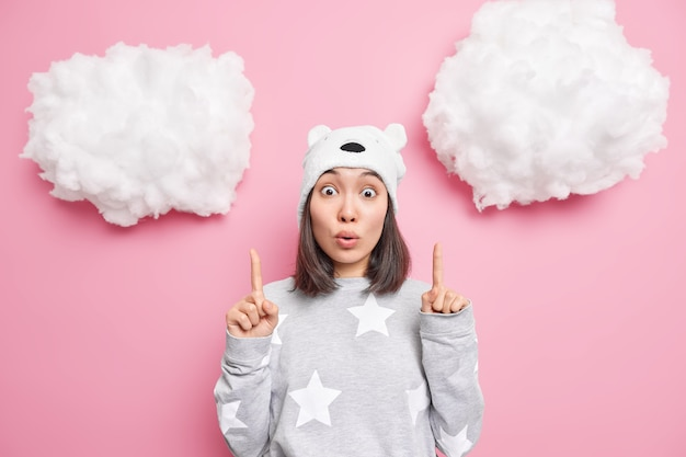 Vrouw met donkere haarpunten boven op witte wolken draagt comfortabele pyjama heeft starre gezichtsuitdrukking poses op roze